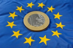 Euromünze auf Europaflagge